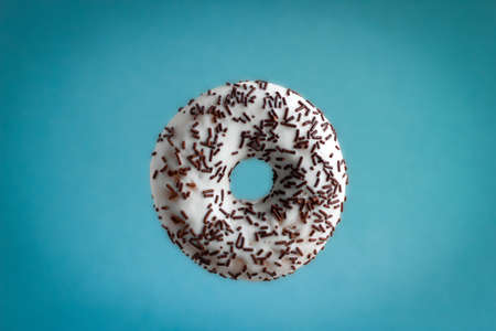 sweet donut with white chocolate icing and chocolate candy sprinkles flying on blue background Banco de Imagens