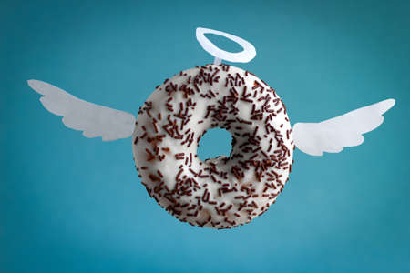 sweet donut with white paper wings and nimbus on a  blue background
