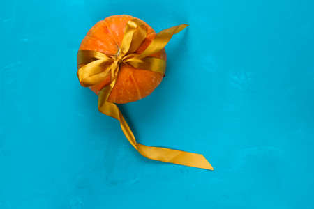 top view pumpkin decorated golden satin ribbon on a blue background copy space