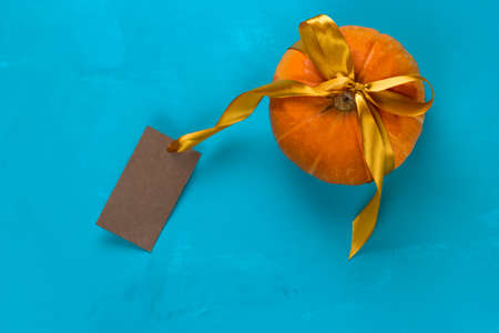 top view pumpkin decorated golden satin ribbon and mock up empty vintage paper label  on a blue background Banco de Imagens