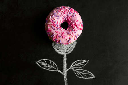 top view donut on chalk board with chalk drawn stem and leaves Banco de Imagens