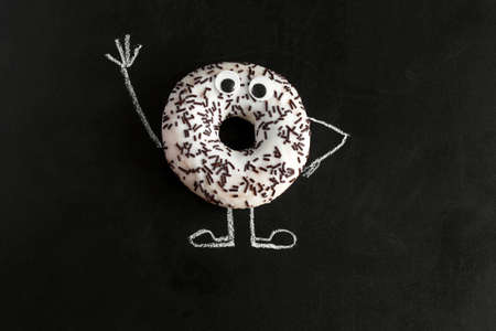 top view donut on chalk board with chalk-drawn arms and legs and googly eyes