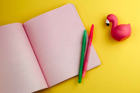 notebook with empty sheets, pencils and cute flamingo eraser on yellow background ,back to school mock up Banco de Imagens