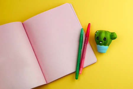 notebook with empty sheets, pencils and cute cactus eraser on yellow background,back to school mock up