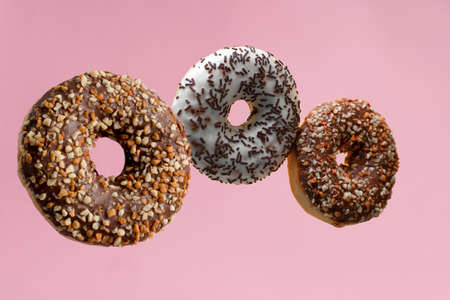 sweet donuts with sprinkles on pastel pink background