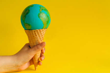 female hand holds waffle cone with Earth model Banco de Imagens