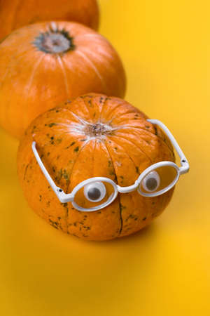 funny autumn card pumpkin with eyes and glasses on a yellow background