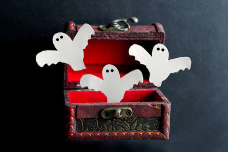 paper cut scary ghosts fly out of an old vintage  wooden chest on a black background, festive Halloween card