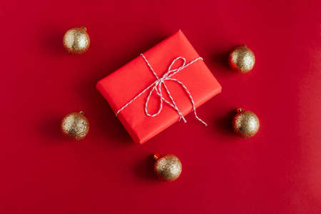 top view red gift box and golden christmas balls on a red background