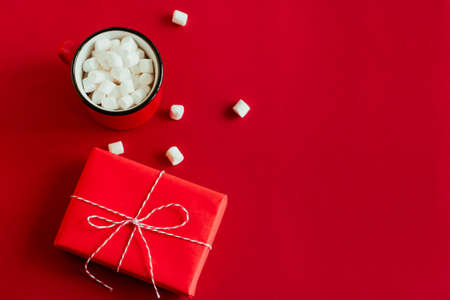 top view red gift box and cup with marshmallows on red background copy space