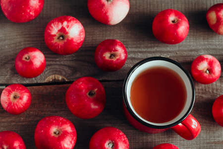 top view apple drink in a red cup and ripe red apples on a wooden background Banco de Imagens