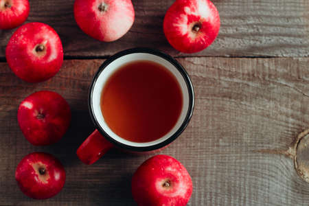 top view apple drink in a red cup and ripe red apples on a wooden background copy space