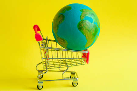metal shopping cart with a model of the planet Earth inside on a yellow background