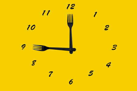 lunch time concept, dial and black plastic forks instead of arrows on yellow background 免版税图像