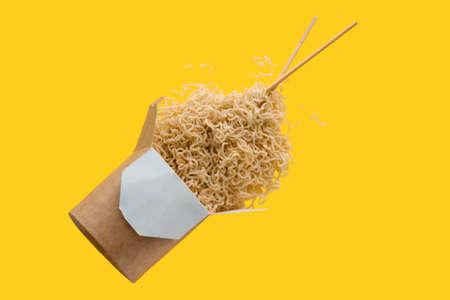 Instant-Nudeln mit Stäbchen, die auf gelbem Hintergrund fliegen, asiatisches Fastfood