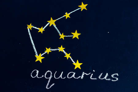 constellation Aquarius drawn in chalk and gold stars on a chalkboard looking like a night starry sky