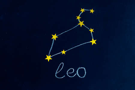 constellation Leo drawn in chalk and gold stars on a chalkboard looking like a night starry sky