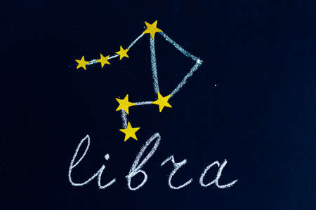 constellation Libra drawn in chalk and gold stars on a chalkboard looking like a night starry sky