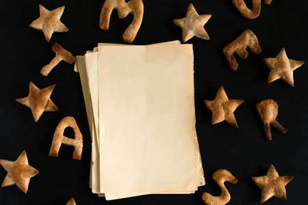 top view flat lay pattern of ginger cookies shaped like stars and letters merry Christmas and sheets of vintage blank paper with space for text on a black background Imagens