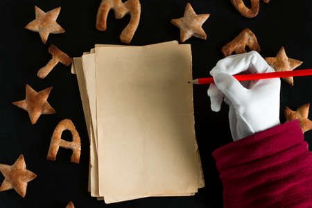 top view flat lay pattern of ginger cookies shaped like stars and letters merry Christmas and sheets of vintage blank paper with space for text and Santa Claus hand in white glo  on a black background