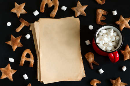 top view flat lay  ginger cookies shaped like stars and letters merry Christmas and sheets of vintage blank paper with space for text and red mug with marshmallows  on a black background