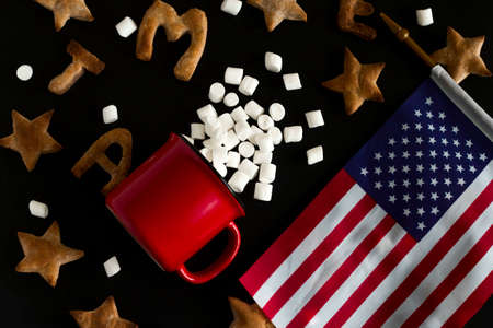 top view flat lay pattern of ginger cookies shaped like stars and letters merry Christmas , red mug with marshmallow mess and USA flag on a black background