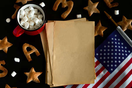 top view flat lay pattern of ginger cookies shaped like stars and letters merry Christmas , red mug with marshmallow , vintage rough blank mock up paer  and USA flag on a black background