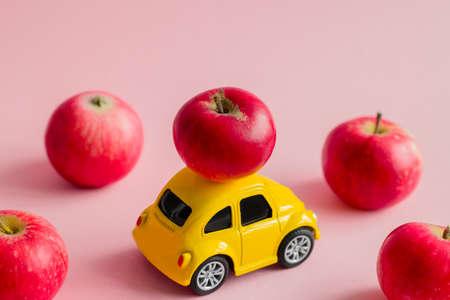 little yellow bauble car with red apples on a pastel pink background