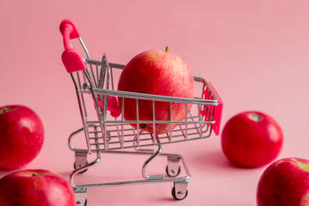 little metal shopping cart with red apples on a pastel pink background, healthy eating and autumn apple harvest concept