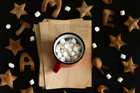 top view flat lay  ginger cookies shaped like stars and letters merry Christmas and red mug with marshmallows  on a black background