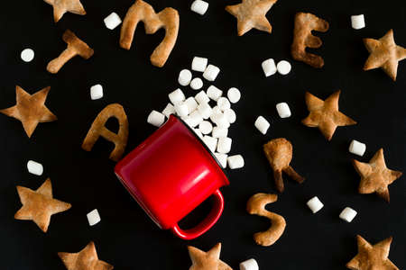 top view flat lay pattern of ginger cookies shaped like stars and letters merry Christmas and  red mug with marshmallow mess  on a black background Imagens