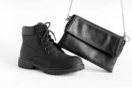 black heavy duty female boots  and fashionable leather clutch on white background Imagens