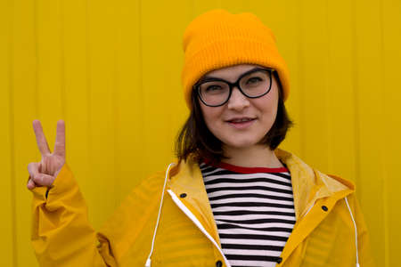 beautiful happy woman wearing  yellow hat and yellow raincoat standing against yellow wall and posing with victory sign Imagens