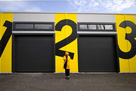 woman in yellow raincoat standing  near wall with numbers one, two,three Imagens