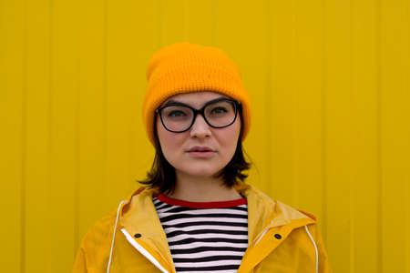 candid portrait of caucasian woman wearing yellow hat,glasses and raincoat standing against yellow wall and looking at the camera