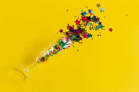 top view flat lay champagne glass with colorful confetti stars on a yellow background