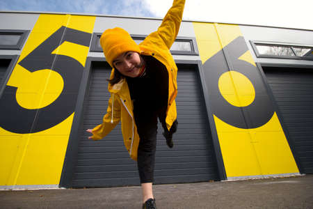 happy young caucasian woman wearing a yellow hat and a yellow raincoat dancing on a city street watching at the camera , positive active lifestyle and street fashion concept