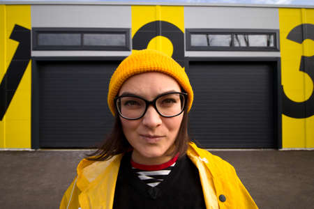candid head shot  portrait of a caucasian woman wearing glasses and a yellow cap looking into the camera