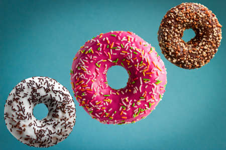 sweet  glazed donuts flying over blue background, junk food concept Imagens