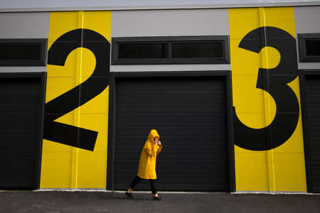 woman in yellow raincoat walking from number two to number three Imagens