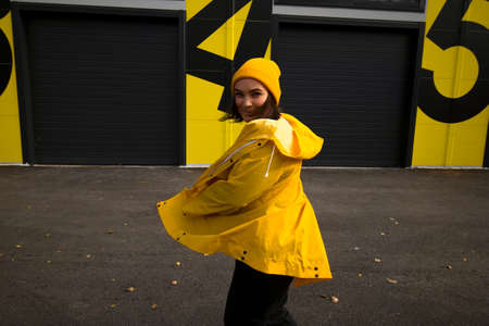 beautiful young caucasian brunette girl wearing hat and yellow raincoat turns around and looks at camera on city street