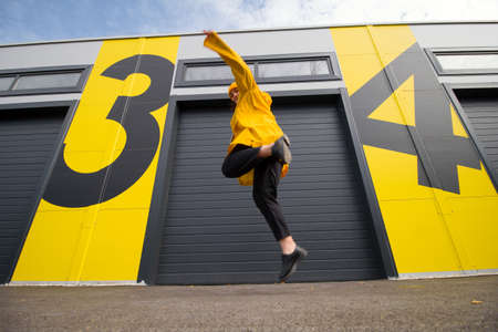young caucasian woman wearing a yellow hat and a yellow raincoat jumping on a city street, positive active lifestyle and street fashion concept