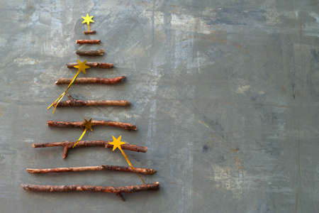 top view flat lay silhouette of a christmas tree made of wooden twigs decorated with gold stars sequins on a gray concrete background with space for text