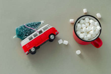 top view minimal  flat lay with red cup with marshmallows and bauble christmas tree on retro toy red truck ,winter holidays concept