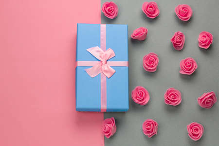 top view blue present box with pink bow and delicate pink roses pattern on a gray and pink background with free space for text