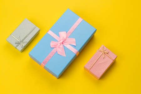 俯视图三个明亮的礼物盒上充满活力的黄色背景
