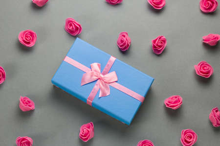 top view flat lay luxury blue present box with festive pink  satin ribbon bow and delicate pink roses pattern on a gray background