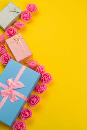 gift boxes and pink roses flat lay on a vibrant yellow background with free space for text Stock fotó