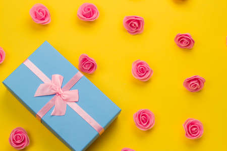 top view flat lay luxury blue present box with festive pink  satin ribbon bow and delicate pink roses pattern on a yellow background