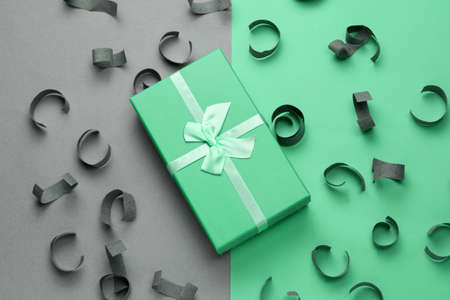 soft green gift box with festive bow top view on a gray and mint background with paper confetti